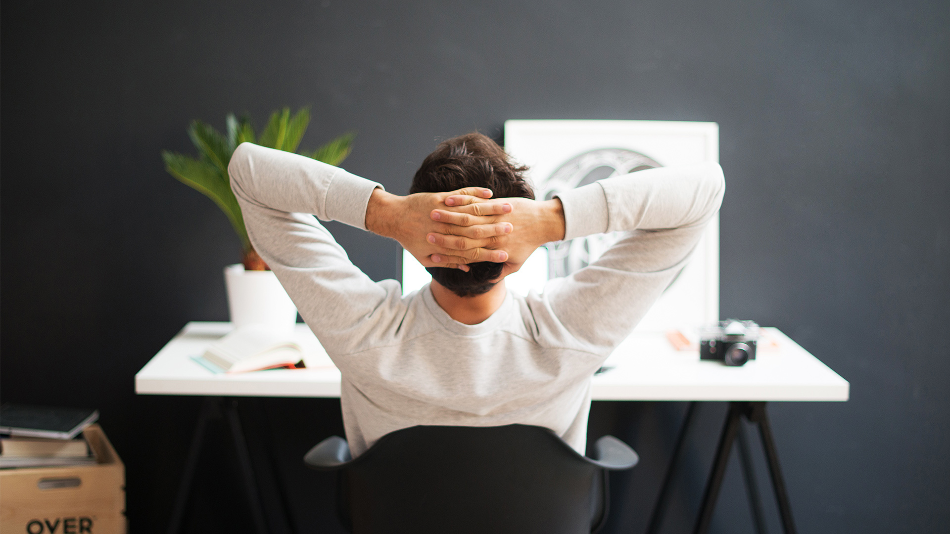 Relaxed arms on head at desk